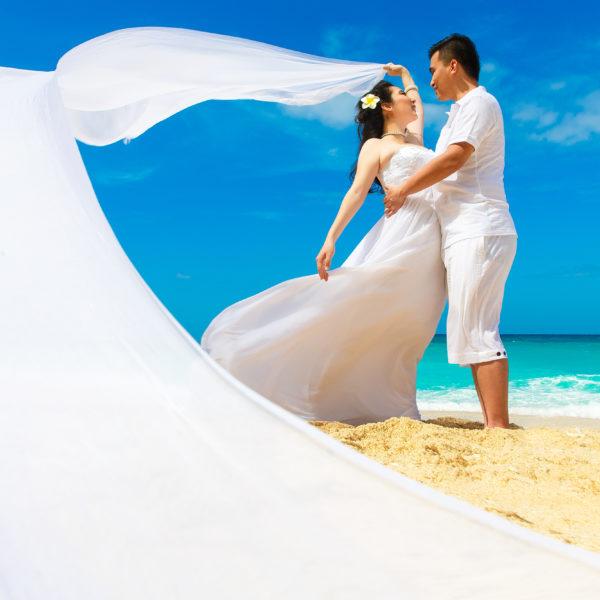 Asian bride and groom on a tropical beach. Wedding and honeymoon