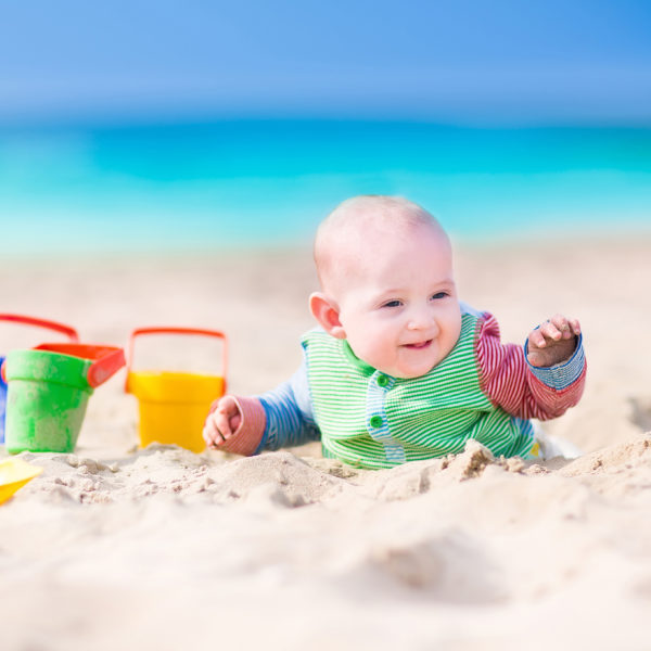 Adorable happy laughing little baby boy in a colorful sun protection suit playing with green, yellow and blue toy bucket and plastic shovel digging in sand on a beautiful exotic tropical beach with turquoise water