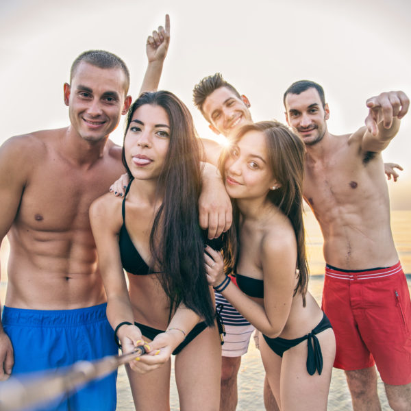Multiethnic group of friends enjoying vacation  and taking a picture with camera - Mixed group of several people having fun on the beach at sunset