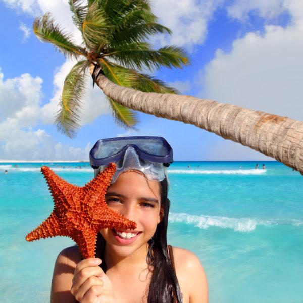 latin tourist girl holding starfish in tropical beach